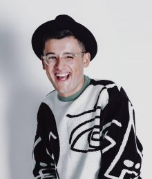 Michael Chakraverty wearing black and white jumper, black trousers, glasses and black hat standing against white background