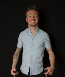 Ricky Balshaw smiling, wearing short sleeve blue shirt showing tattoo on his right arm
